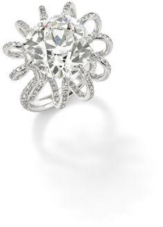 A diamond ring  The cushion-cut diamond, weighing 15.50 carats, claw-set within a pavé-set diamond spiralling bezel, to a similarly set diamond shank.