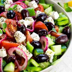 This Greek salad is a healthy vegetable packed appetizer drizzled with a homemade red wine vinegar dressing. Each serving contains creamy feta cheese, kalamata olives, tomatoes, bell peppers, cucumbers and red onion. #video #greeksalad #salad