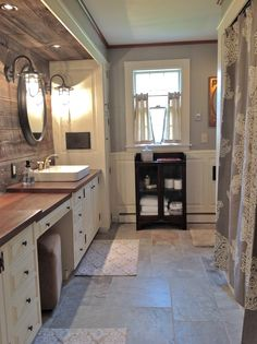 Unusual materials used in this gorgeous farmhouse bathroom.  Barnwood walls, nautical light sconces, wood counters, slate floor....very pretty