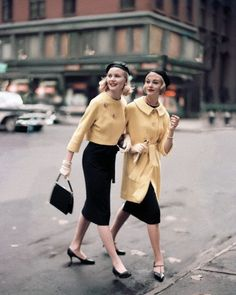 February 1958    The model on the left wears a classic navy sheath with short yellow jacket by Jeanne Campbell for Sportwhirl, beret by John Frederics Charmer    The other wears knee-high coat by Jeanne Campbell for Sportwhirl , T-strapped shoes by Fortunet, necklace by Colette, Kislav gloves, and a Capador beret.    Image by © Condé Nast Archive/Corbis