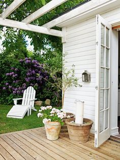 White exterior, white painted timber pergola.  Natural timber deck... and a pretty green garden of course