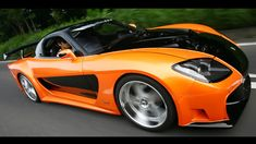 1997 Mazda RX-7..Universal Studios found Han's 1997 RX-7 at the 2005 Tokyo Auto Show and was originally showcased as a Veilside-tuned Japanese sportster.  When the Universal film team saw the car they decided to buy the car as is and changed the car's body color from a red/burgundy and black finish to a more audience-capturing bright orange and black finish while leaving the Veilside kit in place.