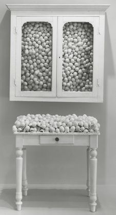 """Marcel Broodthaers. White Cabinet and White Table. 1965.  Painted cabinet, table, and eggshells.  Broodthaers often used found or discarded materials, favoring eggshells, which are """"without content other than the air."""" Using antique-looking furniture and organic materials, Broodthaers critiqued museum display and avoided modern products. In 1968, he created his own museum—called Museum of Modern Art—in his apartment, complete with labels and a catalogue."""