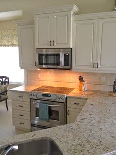 ivory kitchen cabinets with glaze. colonial cream granite counter. handmade beach color subway tile with decorative pencil trim