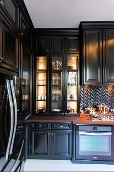 all black kitchen of the year for 2014 by Steven Miller - Kraftmaid onyx lighted upper cabinet - Kraftmaid via atticmag