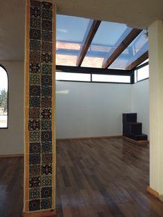 Se construyo un techo de vidrio con vigas de madera y se forro el piso con duela de madera natural, se forraron unas escaleras y una columna de talavera lisa color azul y con figuras para dar un remate visual diferente al espacio con techo de vidrio.