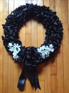 Condolence wreath I made with black wired ribbon, different textures including satin ribbon. Needed are 60 yards total of different wired ribbon, wire wreath assembly and silk flowers. Cut ribbon to 18 inch pieces, 8 pieces per area of wreath assembly. Tie know in each piece around two wires going around the death assembly starting in the middle of the wreath assembly. Once done fluff and add flowers. Can be done with real flowers if using a plastic reservoir on each stem.