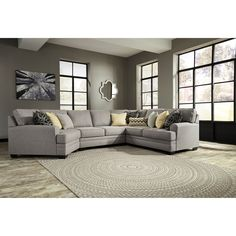 Update your living room with the contemporary style and comfort of this sectional with a cuddler. Rounded track arms, loose back cushions, and T-style seat cushions, along with a gray fabric and stylish accent pillows, all contribute to a sophisticated contemporary feel.