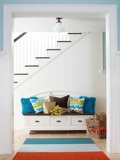 A fun storage bench in a hallway is not just pretty but functional. A hidden drop zone for hats, gloves and shoes!