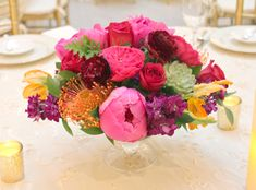 Hot pink bright orange and deep purple compote centerpieces with succulents, protea and peony