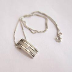Ontwerp van Karen Klein edelsmid. Strak zilveren hangertje met mat/glans banen en rechthoekige raampjes.