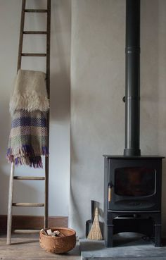Great idea for by the wood burner, cosy throws kept nearby on a wooden ladder