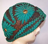 This vintage Art Deco teal felt embroidered gold lace flapper cloche hat dates from the roaring 1920s. The hat is made of a sheer gold metallic lace net stitched fabric base, with a blue green teal color felt done in a decorative embroidered stitch floral daisy design with gold leather padded centers. This fabulous form fitting flapper cloche hat has a rolled brim front and is sheer unlined inside.