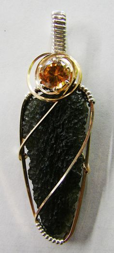 Moldavite wrapped in 14K GF and Sterling with a Topaz colored CZ.