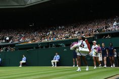 Serena Williams and Angelique Kerber walk onto Centre Court for the final