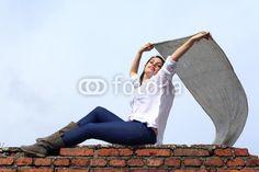 Ragazza sul muro con foulard al vento