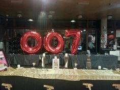 www.la-occasion.com - James Bond Themed Party  007 Large Red Foil Balloon, with Spy Men Cutout stuck on.   Black Table Cloth with Gold Satin Runners with Playing Cards and small cocktail glasses with dices and playing cards, golden guns.