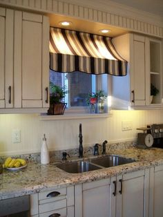An interesting way to dress a kitchen window in between cupboards.