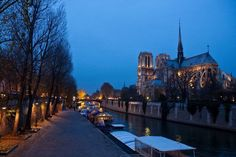 """Notre Dame at Dusk  Photograph by Rick Wianecki   I took this photograph in the early dusk, when the lights of Notre Dame just flickered """"on"""" and the daylight seemed to be melting away through various shades of blue. It was a memorable end to a great day of tramping through the streets of Paris."""