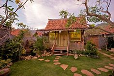 my dream is living in an antique Javanese village house  with hand-hewn wooden beams, intricate carvings, and a rustic . design.---The Kampung, Amed- Bali