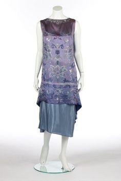 1926 Callot Soeurs embroidered orientalist cocktail dress, unlabeled, embroidered in floss silks in shades of blue and white with Chinese-style flower heads and foliage, with draped, pointed rear skirt panel; together with a pale blue silk petticoat. Via Live Auctioneers.