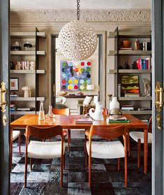 Love this midcentury modern + glam design  from the unique bookcases to the dope chairs..