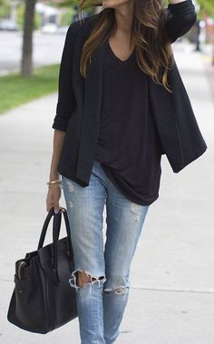 Black wrap sweater, slouchy, strategically tucked-in tee, and distressed denim look sleek, not sloppy with a luxe tote, accessories, and soft waves.