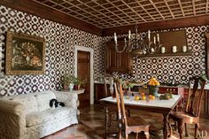 Studio Peregalli ~ kitchen - The kitchen's La Cornue range and hood match the tone of the majolica tiles that Studio Peregalli used on the walls; an early-20th-century bronze chandelier is suspended over the Carrara marble–top table and antique dining chairs, while a 17th-century still life hangs above the dog's linen-upholstered perch.