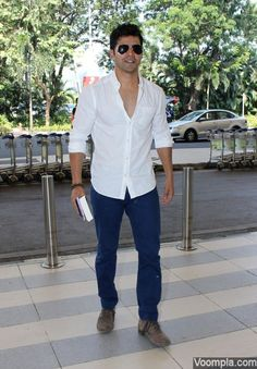 A clean shaven Varun Dhawan looks hot in an unbuttoned white shirt, jeans, boots and dark aviator style sunglasses. via Voompla.com