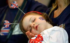 A young fan takes a nap during the women's handball match between Russia and Great Britain at the Copper Box venue