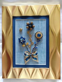 """Sapphire Pride"" 5""x7""  This enchanting trio of flowers happily wave above a gorgeous gold toned ribbon base made of royal blue enamel outlined with clear glass rhinestones. The Lisner flower (circa 1904-1979) in the middle is a circle of fine gold colored filigree beads interspersed with glass bicone beads with a large faceted round glass bead in the center. The rope style chain stem is adorned with tri-tipped fine filigree leaves. The Jonne flower (circa 1950's-1962) on the left is made of…"