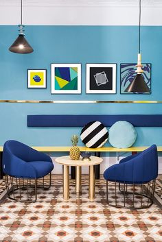 Wall Decor Inspiration - Bold Graphics Cover The Walls Of This Spanish Hostel // Various shades of blue are broken up by artwork and gold/yellow touches.