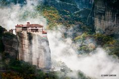 Clouds roll past the cliff-top Monastery of Rousanou in Meteora, Greece.