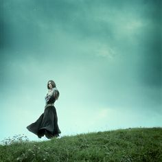 Standing on a hill with dark clouds, wind, and a flowing skirt. Love.
