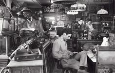 Man reading in antique store, Second Avenue, New York, June 1969 by Andre Kertesz