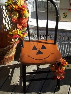 Pumpkin Chair from A Sentimental Life: Vintage Finds.  Seat of chair painted with jack-o'-lantern face for Halloween.