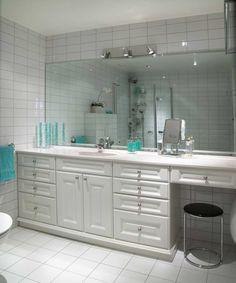 Baderomsinnredning med heldekkende benkeplate og integrert vask i kompositt. Profilerte dører og møbel sokkel. Stort speil og innebygget sminkebord