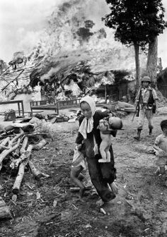 With a few salvaged belongings in the background, a Vietnamese woman carries a baby and pulls her daughter away as their home erupts in flames in July 1963. The woman and children may have been left behind so as not to slow other villagers escaping into the jungle. (AP Photo/Horst Faas)