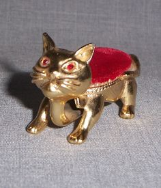 """Vintage Florenza cat nodder pin cushion. This piece measures app. 2 ½"""" long and has its original red rhinestone eyes and red velvet pin cushion."""