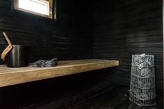 Selkeälinjaisessa ja tunnelmallisessa saunassa on tyylikkään mustat seinät sekä puinen tasolaude.