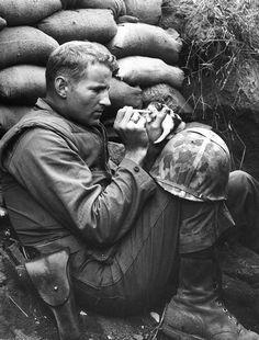 Sargento marinho Frank Praytor, que alimenta um gatinho órfão. O homem adotou a cria após a mãe morrer durante a guerra.