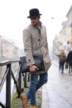 Opt for a grey overcoat and blue skinny jeans if you're going for a neat, stylish look. Tan suede boots are a perfect choice to complete the look.  Shop this look for $389:  http://lookastic.com/men/looks/hat-longsleeve-shirt-overcoat-zip-pouch-skinny-jeans-boots/4879  — Black Wool Hat  — Grey Longsleeve Shirt  — Grey Overcoat  — Black Leather Zip Pouch  — Blue Skinny Jeans  — Tan Suede Boots