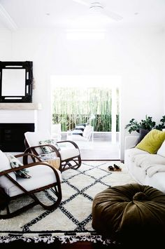 Stunning, clean living room design featuring white walls, diamond printed rug, cozy couch, a built-in fireplace and Lincoln Brooks 'Pretzel' chairs | Styled by Natalie Walton