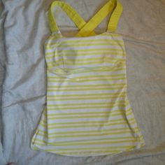 Lululemon yellow& white tank Good condition,  there is some pilling on the back,  it is 1inch wide by 5 inches long,  see pic #4, size is a guess, bra is padded, armpit to armpit is 12 inches. I am fairly confident this is a size 2, however size is a guess lululemon athletica Tops Tank Tops