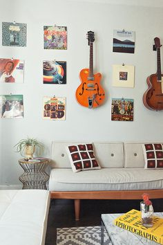 "Sneak Peek: Chelsea and Forrest Kline. ""This is our music room (Forrest has dubbed it the 'music enjoyment facility') which doubles as our guest room. We hung a bunch of our favorite records on the wall with binder clips for easy access. Forrest also hung some of his guitars on the wall so he can mess around in there while listening to records."" #sneakpeek"