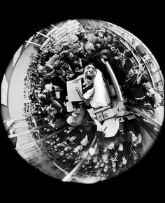 """Salvador Dali at a book signing, taken with a fisheye lens, by Philippe Halsman, 1963."""