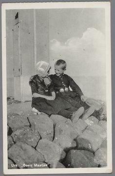 Kinderpaar in Urker dracht zittend op basaltblokken, waarbij de jongen een arm om het meisje heeft geslagen. Hij draagt Urker broeksknopen. 1930-1942 #Urk