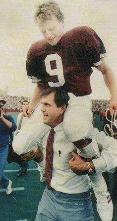 Texas A & M head coach Jackie Sherrill carries quarterback Craig Stump (#9) off the field after beating Arkansas.-11/14/87