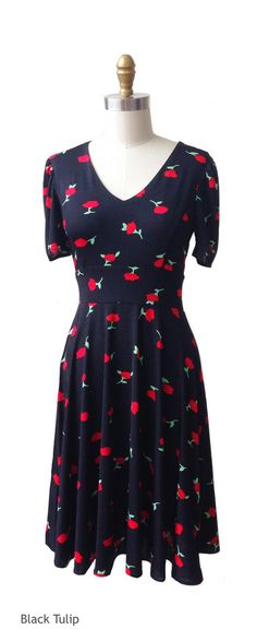 The Mary, shown here in the black tulip print, is a short sleeve dress with a knee length skirt & full coverage neckline. The Mary is a great dress for every body type!