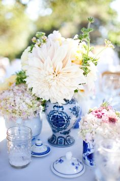 centerpieces of blue and white Chinese vases and teapots filled with flowers